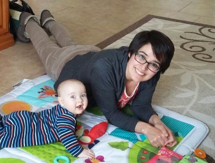 Woman lying on ground with baby